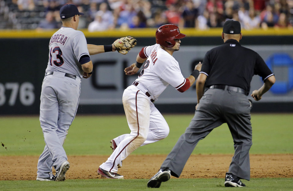 Photo - Arizona Diamondbacks' Gerardo Parra eludes the tag of Cleveland Indians' Asdrubal Caabrera (13) as umpire Vic Carapazza watches during the sixth inning of a baseball game, Tuesday, June 24, 2014, in Phoenix. Parra was ruled safe after avoiding the tag in a rundown. (AP Photo/Matt York)