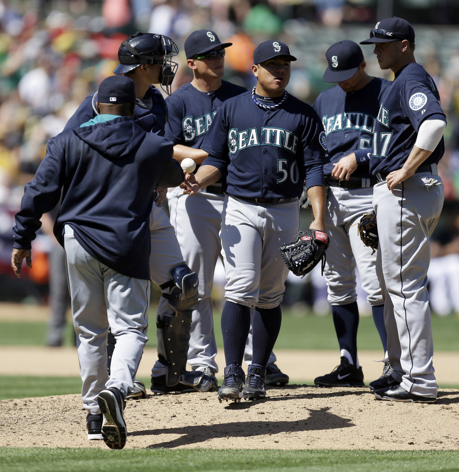 Photo - Seattle Mariners' Erasmo Ramirez (50) hands the ball to manager Lloyd McClendon as he is removed from the baseball game against the Oakland Athletics in the fifth inning Sunday, April 6, 2014, in Oakland, Calif. (AP Photo/Ben Margot)