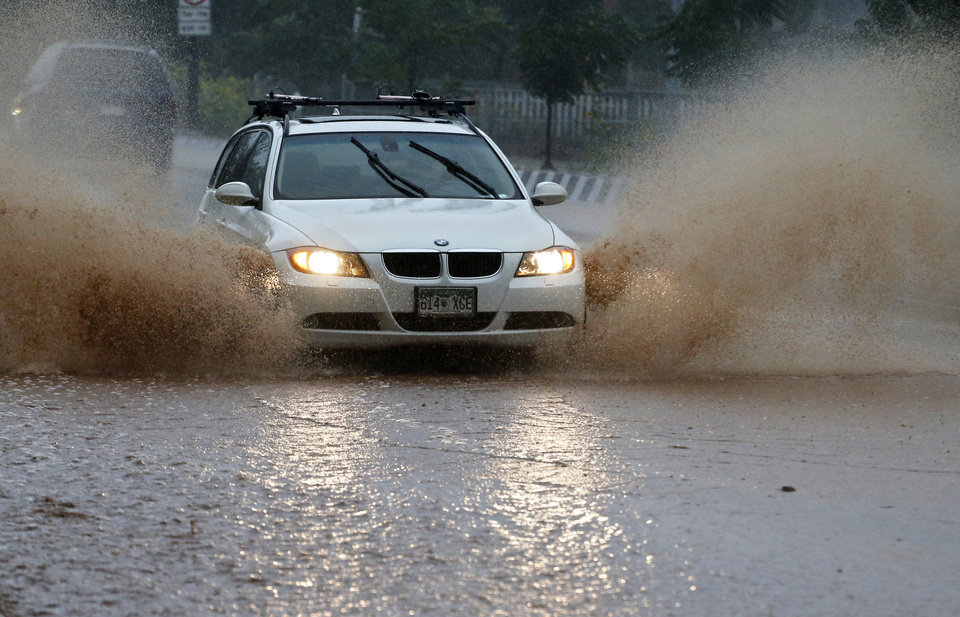 Photo - A car drives on a flooded road following overnight flash flooding in downtown Boulder, Colo., Thursday, Sept 12, 2013. The widespread high waters are keeping search and rescue teams from reaching stranded residents and motorists in Boulder and nearby mountain communities as heavy rains hammered northern Colorado. (AP Photo/Brennan Linsley)