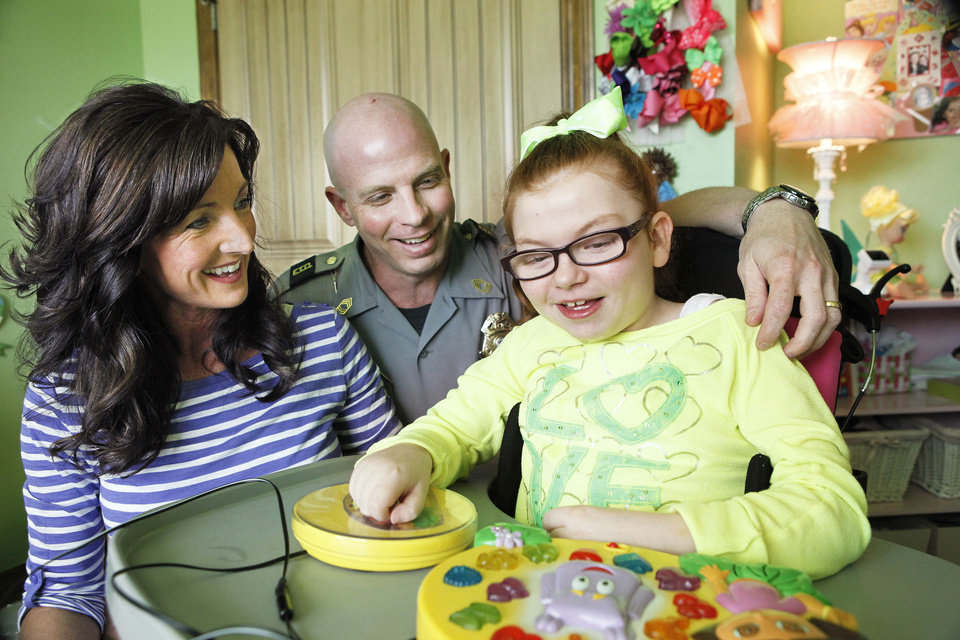 Photo - Brenda and Mike Greene, of Oklahoma City, are shown with their daughter, Macie, 9, who has Rett syndrome. Photo by David McDaniel, The Oklahoman