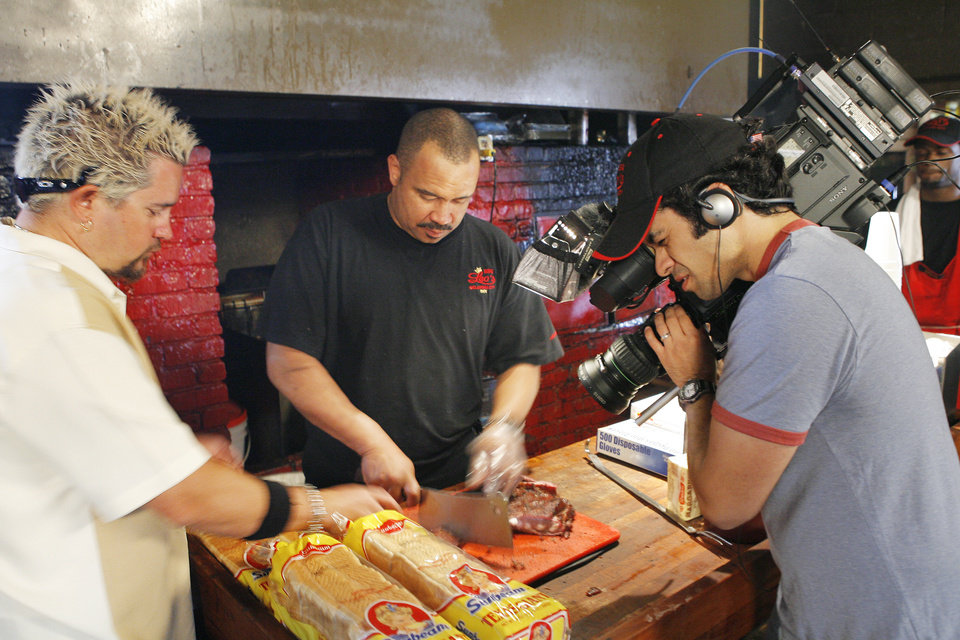 Photo - BARBECUE RESTAURANT: Food Network star Guy Fieri tries to get a rib as Leo's BBQ owner Charles Smith cuts them during the filming of