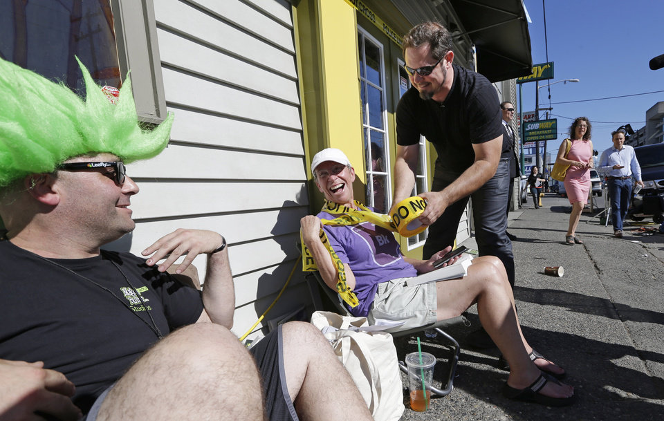 Photo - Cannabis City owner James Lathrop, right, playfully wraps up first-in-line customer Deb Greene in