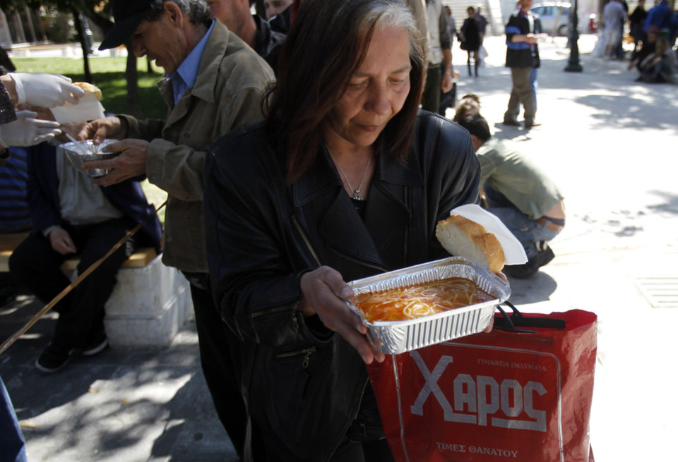 Photo -   A woman receives a free meal during a soup kitchen organized by a Greek humanitarian group in Athens' main Syntagma square on Sunday, April 1 2012. Greece's austerity cutbacks have deepened the economic recession, and torn holes in the country's social fabric. Unemployment has hit a record high of 21 percent, and thousands of Greeks depend on church and municipal soup kitchens for sustenance. (AP Photo/Kostas Tsironis)