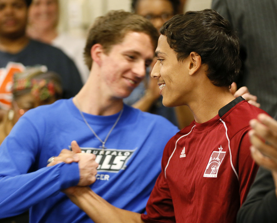 Photo - Matthew Giudice, right, gets a hug from teammate Austin Place during the signing day ceremony at Edmond Santa Fe High School in Edmond, Okla., Wednesday, Feb. 6, 2013. Place will play soccer for the University at Buffalo. Giudice will play soccer and run track for Hastings College. Photo by Nate Billings, The Oklahoman