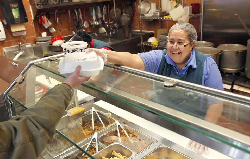 Photo - Maria Perez prepares a customer's meal at Supermercado Morelos on Feb. 6 in Moore.  Photo by Paul Hellstern, The Oklahoman  PAUL HELLSTERN - Oklahoman