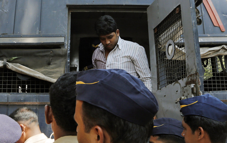 One of four men convicted of gang raping a photojournalist  in India's financial capital of Mumbai last year stands inside a police van as he is brought to prison, in Mumbai, India, Thursday, March 20, 2013. The Mumbai court is expected to sentence the men on Friday, said Maharashtra state Home Minister R.R. Patil. The four face a minimum of 20 years in prison, and could receive life sentences, said Prosecutor Ujjwal Nikam. (AP Photo/Rajanish Kakade)