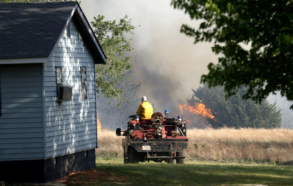 Photo - A firefighter prepares to extinguish flames near by home near East Seward Road and Oak Hill Road,  Sunday, May 4, 2014. Photo by Sarah Phipps, The Oklahoman