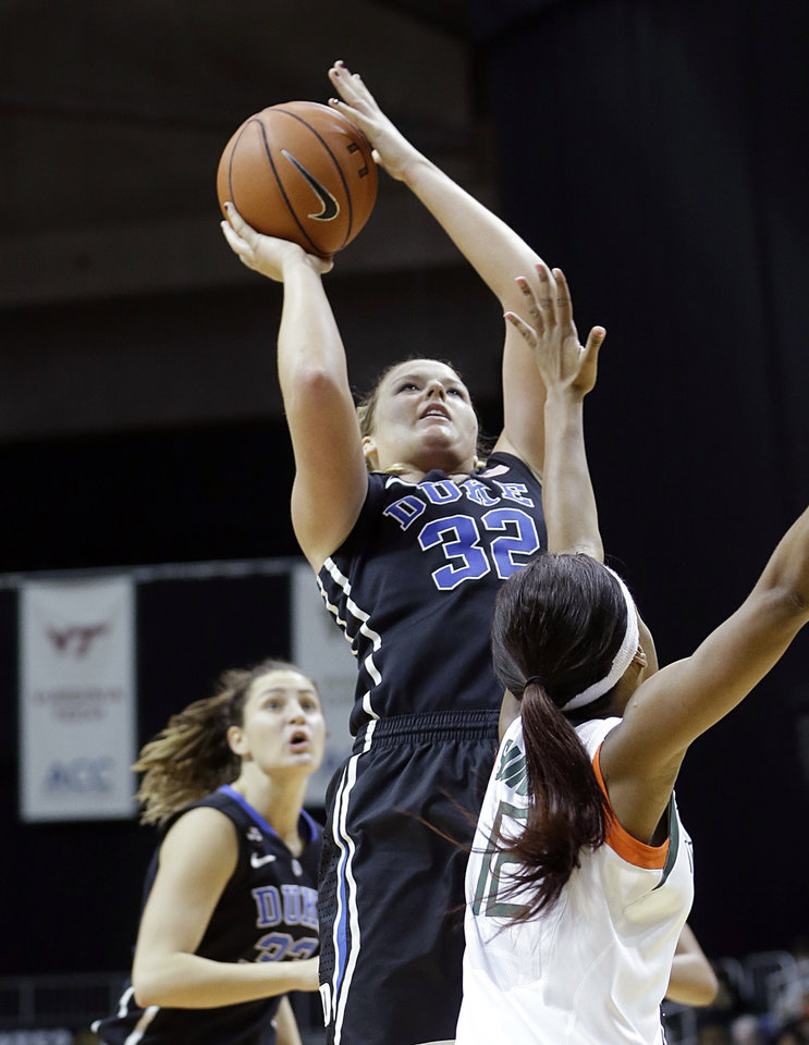 Photo - Duke Blue Devils guard Tricia Liston (32) prepares to shoot over Miami Hurricanes guard Krystal Saunders (12) during the second half of an NCAA college basketball game in Coral Gables, Fla., Thursday, Jan. 30, 2014. Duke won 76-75. (AP Photo)
