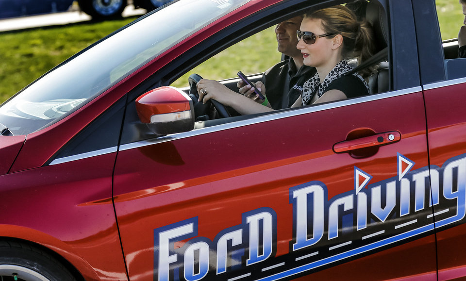Sidney Earnheart tries to text and drive while navigating a course during Ford Driving Skills For Life at Yukon High School on Thursday. Photo by Chris Landsberger, The Oklahoman ORG XMIT: KOD <strong>CHRIS LANDSBERGER - CHRIS LANDSBERGER</strong>