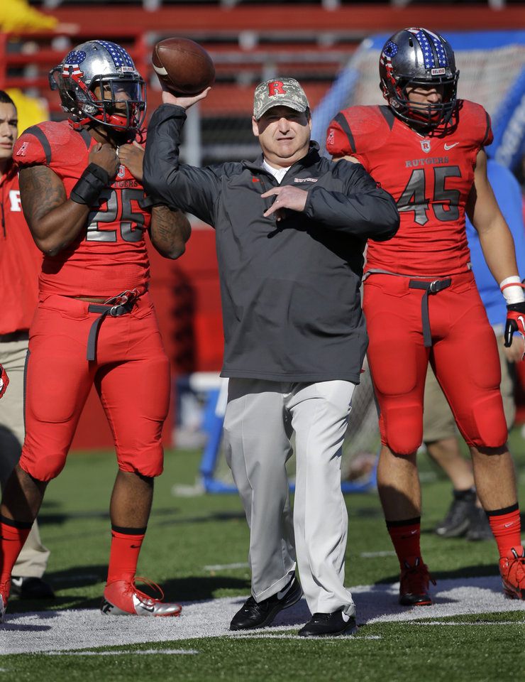 Photo - Rutgers defensive coordinator Dave Cohen throws a football during warm-ups before an NCAA college football game against Cincinnati in Piscataway, N.J., Saturday, Nov. 16, 2013. (AP Photo/Mel Evans)