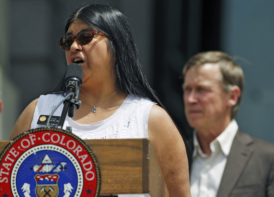 Photo - Colorado State Senator Irene Aguilar, MD, who sponsored a Medicaid bill, speaks during a ceremony at which Governor John Hickenlooper, right, signed into law an expansion of Medicaid eligibility that's expected to add 160,000 adults to public health care assistance, at the state Capitol, in Denver, Monday May 13, 2013. The expansion is part of the federal health care overhaul. (AP Photo/Brennan Linsley)