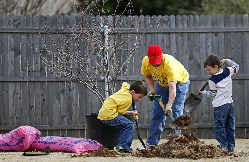 Photo - Steve Lovelace helps his seven-year old son, Jaxon, with Cub Scout Pack 91, and son, Behrend Lovelace, dig a hole to plant a tree at Westborough Park.