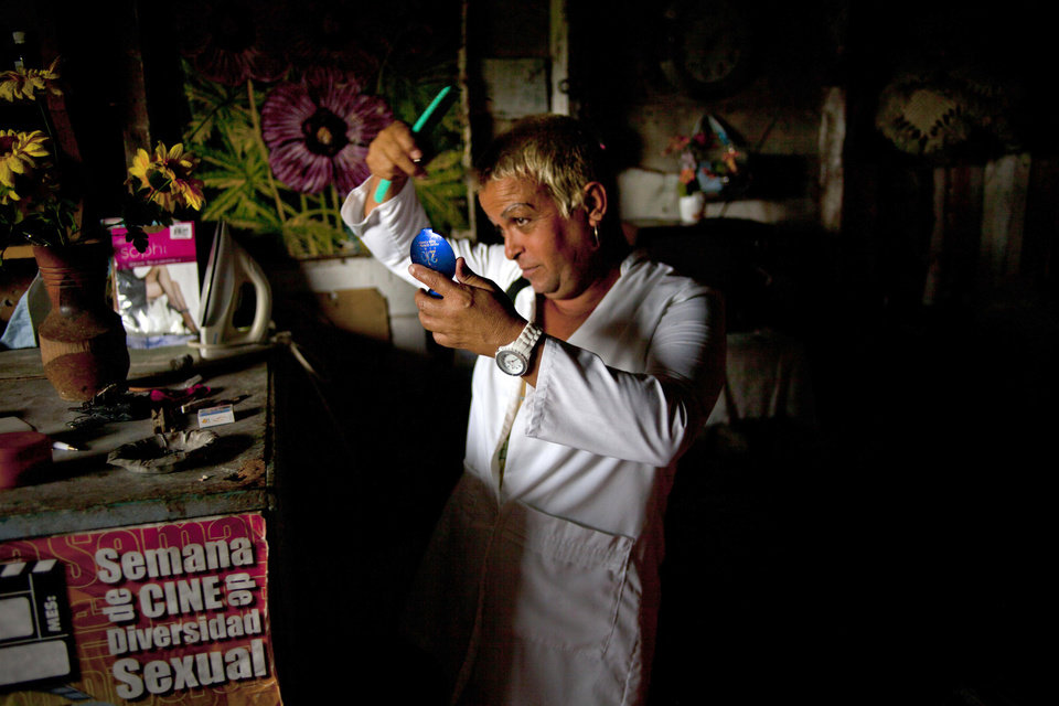 "Adela Hernandez, 48, looks into a compact mirror as she combs her hair at her home home in the village of Caibarien, Cuba, Friday, Nov. 16, 2012. Hernandez, a biologically male Cuban who has lived as a female since childhood, served two years in prison in the 1980s for ""dangerousness"" after her own family denounced her sexuality. This month she made history by becoming the first known transgender person to hold public office in Cuba, winning election as a delegate to the municipal government of Caibarien in the central province of Villa Clara. (AP Photo/Ramon Espinosa)"