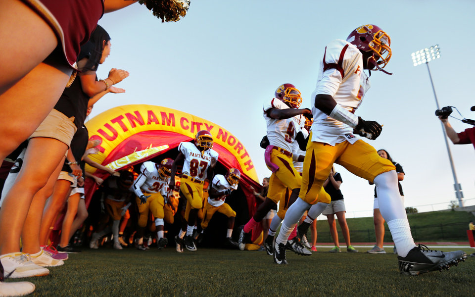 Photo - North takes the field as the Moore High School Lions play the Putnam City North Panthers in high school football on Thursday, Oct. 3, 2013, in Moore, Okla.  Photo by Steve Sisney, The Oklahoman