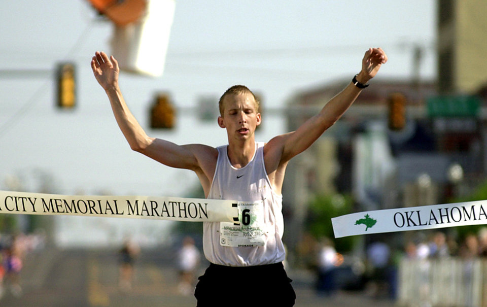 Photo - Peter Euler of Pittsburg, Kan., breaks the ribbon to win the Oklahoma City Memorial marathon Sunday morning.  Staff photo by Bryan Terry