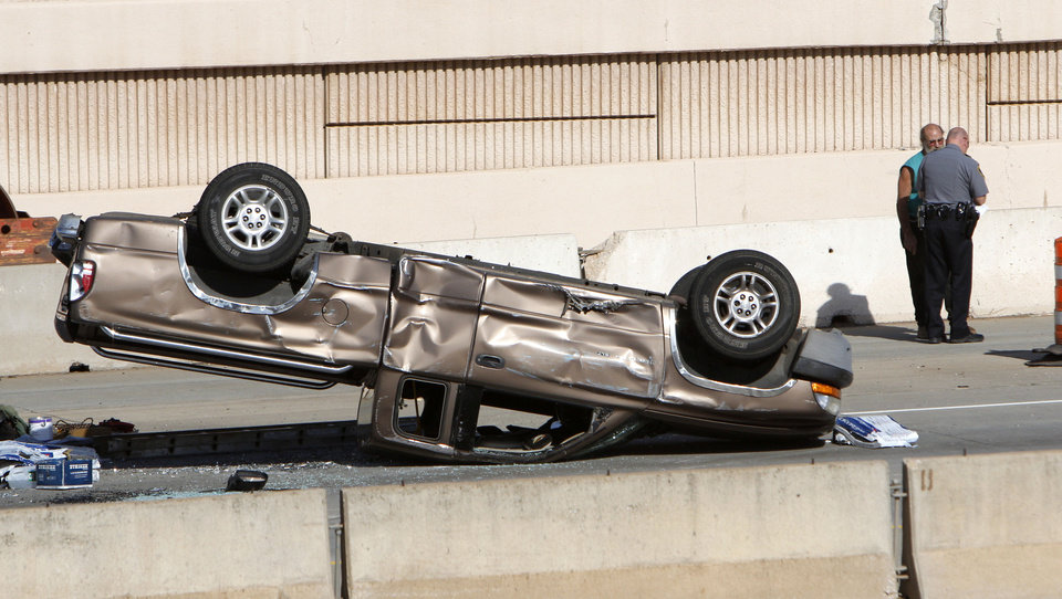 Oklahoma City Police investigate a rollover injury accident which occurred during morning rush hour traffic on the Broadway Extension just north of 63rd St. in Oklahoma City, OK, Thursday, May 17, 2012,  By Paul Hellstern, The Oklahoman