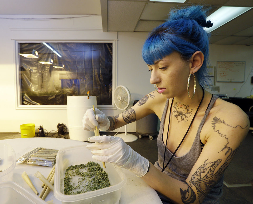 In this photo taken Tuesday, July 1, 2014, Stevie Askew, a worker at Sea of Green Farms, packs recreational marijuana into blunts that will be sold in stores when legal recreational pot sales begin Tuesday, July 8, in Washington state. The grower, the first business licensed to grow recreational marijuana in Washington state, worked all weekend to have supplies ready for stores that were expected to be granted sale licenses on Monday. (AP Photo/Ted S. Warren)