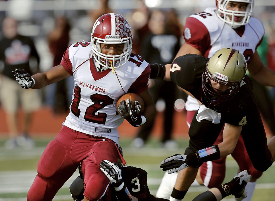 Wynnewood runningback Curtis Rushing tries to escape flying tackler Peyton Maroney. Holding onto Rushing\'s leg is Hunter Suntken. Cashion vs. Wynnewood at Norman in a Class A semifinal football game, Saturday, Dec. 1, 2012. Photo by Jim Beckel, The Oklahoman