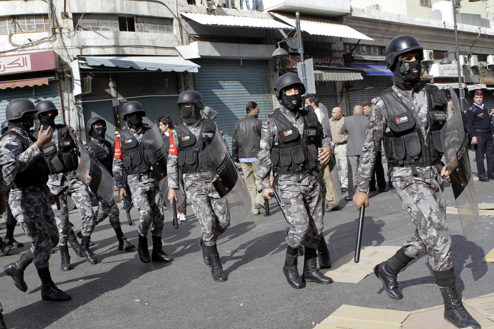 Jordanian riot police approach protesters who tried to bypass a designated demonstration area after Friday prayers in Amman, Jordan, Friday, Nov. 16, 2012. Larger groups have demonstrated in Amman since the unrest sparked by fuel price hikes started three days ago, but Friday�s march constituted the biggest single bloc yet to call for the end of the U.S.-backed monarch�s regime. The crowd of some 2,500 also chanted slogans reminiscent of last year�s uprisings in the region.(AP Photo/Raad Adayleh)