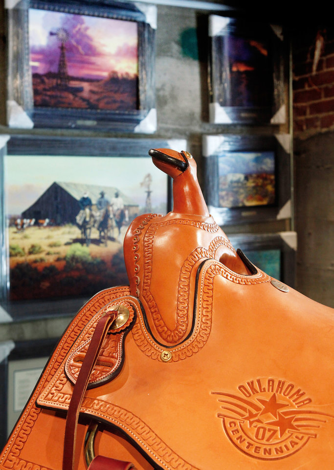 Photo - A custom saddle and western art are among items for sale in the Cross Barr Gallery.  photo by Jim Beckel,  The Oklahoman