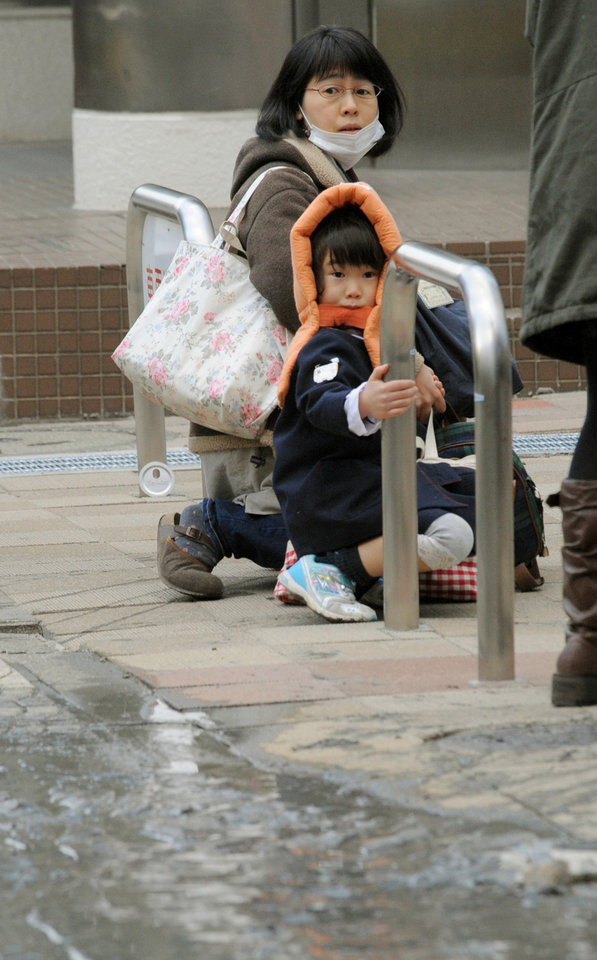 Photo - A mother and child crouch on a street in Tokyo while an earthquake hits Friday, March 11, 2011. Japan was struck by a magnitude-8.8 earthquake off its northeastern coast Friday, triggering a 13-foot (4-meter) tsunami that washed away cars and tore away buildings along the coast near the epicenter.(AP Photo/Kyodo News) JAPAN OUT, MANDATORY CREDIT, FOR COMMERCIAL USE ONLY IN NORTH AMERICA ORG XMIT: TOK811