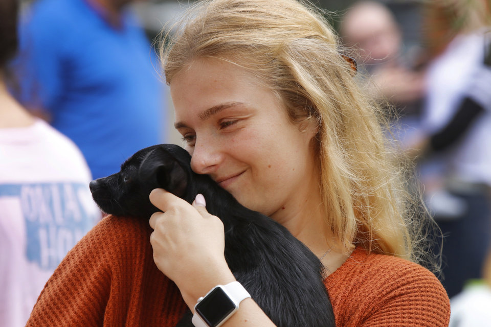 Photo - Victoria Boudiette, an OU pharmacy school student, snuggles a puppy up for adoption during the inaugural Veg Fest on the Great Lawn at the Myriad Botanical Gardens, Saturday, September 8, 2018.  Photo by Doug Hoke, The Oklahoman