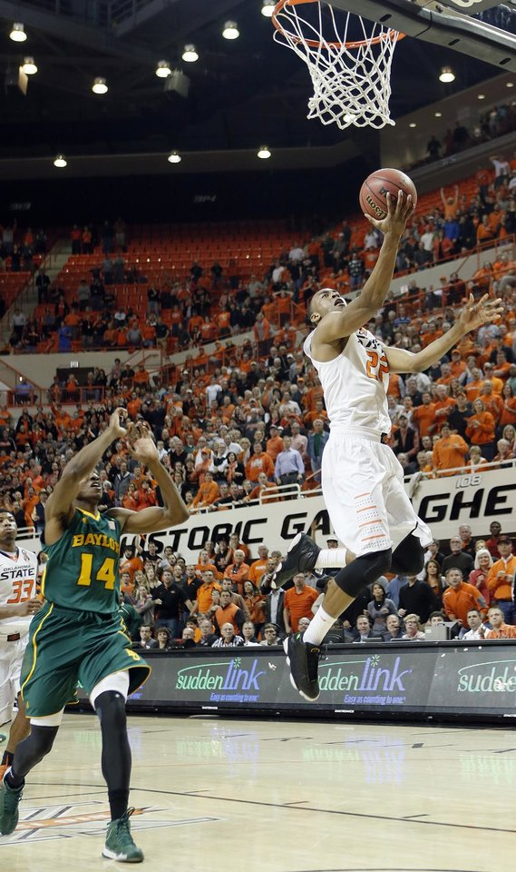 Oklahoma State \'s Markel Brown (22) lays in the game winning shot in front of Baylor\'s Deuce Bello (14) during the college basketball game between the Oklahoma State University Cowboys (OSU) and the Baylor University Bears (BU) at Gallagher-Iba Arena on Wednesday, Feb. 5, 2013, in Stillwater, Okla. Photo by Chris Landsberger, The Oklahoman