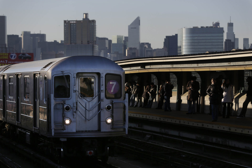 Photo - Commuters wait on the platform as a train passes through the 40th St-Lowry St Station, where a man was killed after being pushed onto the subway tracks, in the Queens section of New York, Friday, Dec. 28, 2012.  Police are searching for a woman suspected of pushing the man and released surveillance video Friday of her running away from the station. (AP Photo/Seth Wenig)