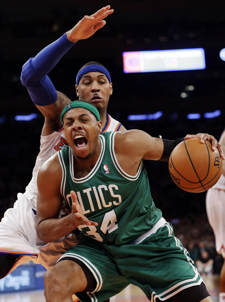 Photo - Boston Celtics forward Paul Pierce (34) reacts as New York Knicks forward Carmelo Anthony, rear, defends in the second half of their NBA basketball game at Madison Square Garden in New York, Monday, Jan. 7, 2013. The Celtics won 102-96. (AP Photo/Kathy Willens)