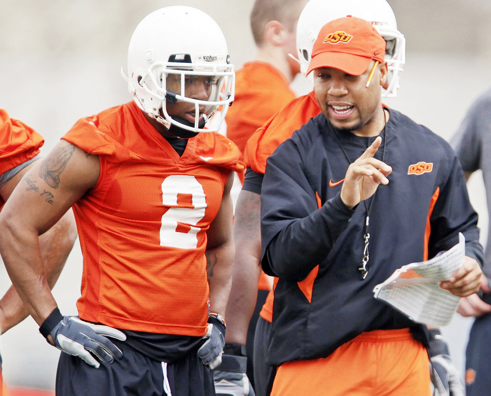 Photo - OSU running backs coach Robert Gillespie, right, talks with Beau Johnson during a spring practice in March. Gillespie isn't known for his gentle style of coaching. (Photo by Nate Billings, The Oklahoman)