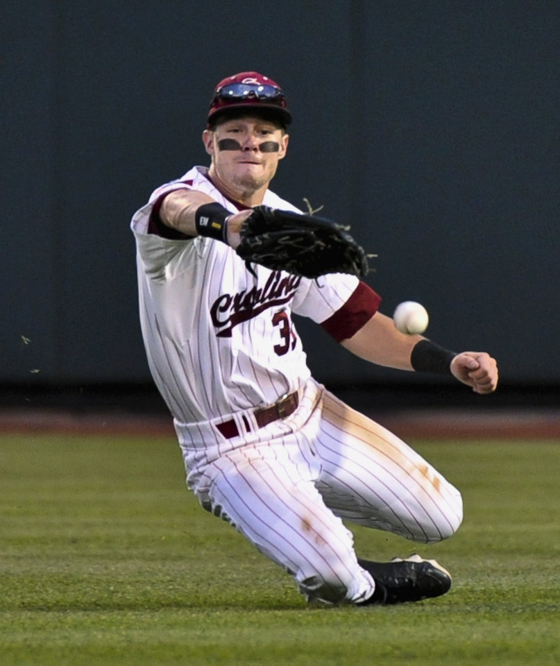 South Carolina�s Evan Marzilli fails to catch a fly ball hit for a double by Arkansas� Tim Carver in the third inning in Omaha, Neb., on Friday. South Carolina won to advance to the finals. AP Photo