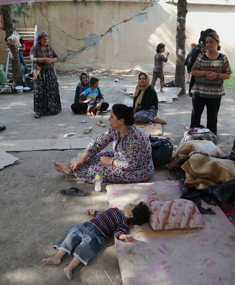 Photo - Displaced Iraqis from the Yazidi community gather at a park near the Turkey-Iraq border at the Ibrahim al-Khalil crossing, as they try to cross to Turkey, in Zakho, 300 miles (475 kilometers) northwest of Baghdad, Iraq, Friday, Aug. 15, 2014. The U.N. this week declared the situation in Iraq a