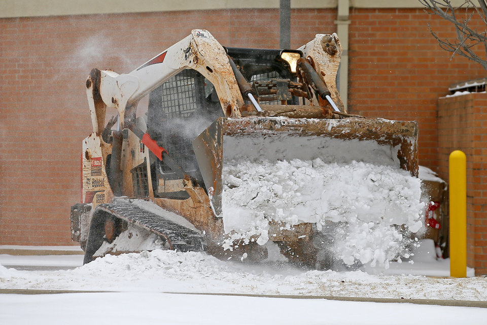 Photo - Raul Ignacio uses a Bobcat to clear snow from the parking lot of a pharmacy in northwest Oklahoma City during a winter storm, Sunday, Feb. 14, 2021. [Bryan Terry/The Oklahoman]