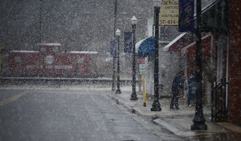 Photo - U.S. Postal employee Janeen Long salts and sands the sidewalk in front of the Exmore, Va. Post Office during a heavy snow fall on Tuesday, March 25, 2014. (AP Photo/Jay Diem, Eastern Shore News) NO SALES
