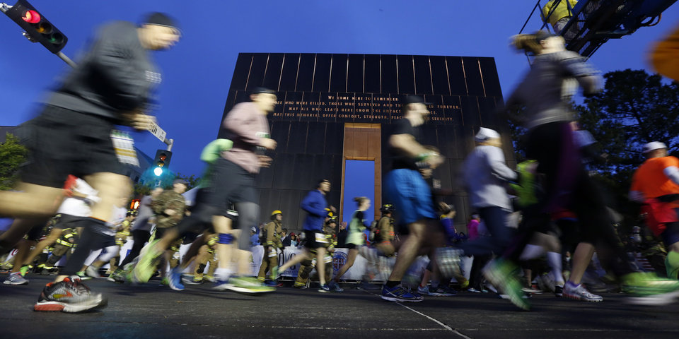 Photo - Runners stream past the 9:03 gate at the start of the 2017 Oklahoma City Memorial Marathon Sunday, April 30, 2017.  Photo by Sarah Phipps, The Oklahoman