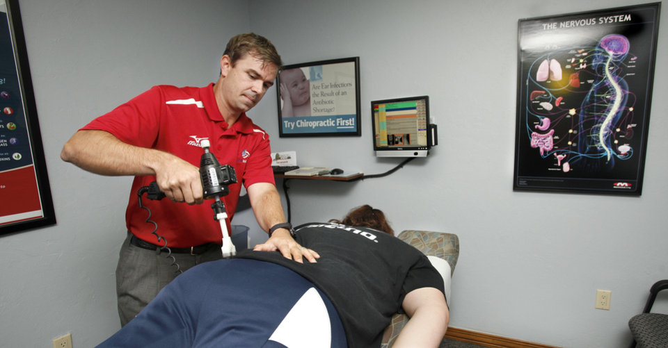 Photo - Dr. Ryan Hanson, an Edmond chiropractor, works on a member of the USA sitting volleyball team before the athletes left for the 2012 Paralympic Games in London. PHOTO BY JIM BECKEL, THE OKLAHOMAN.  Jim Beckel - THE OKLAHOMAN