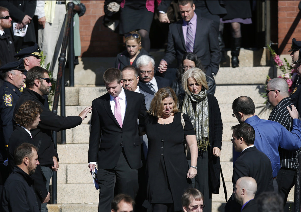 Photo - A mourner reaches out to Daniel Ritzer, brother of slain Danvers High School teacher Colleen Ritzer, as he accompanies his mother, Peggie, out of St. Augustine Church in Andover, Mass., Monday Oct. 28, 2013 after Colleen Ritzer's funeral service. (AP Photo/Elise Amendola)