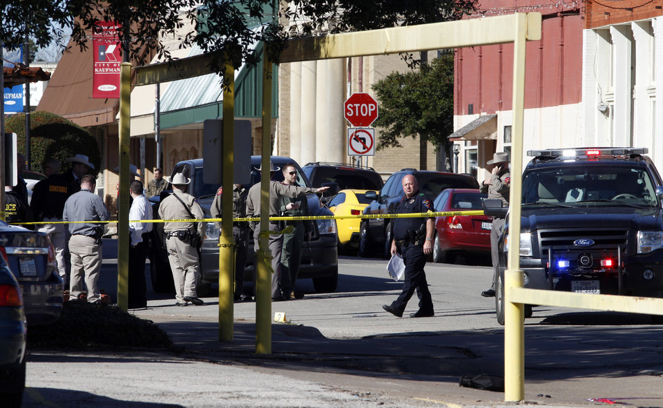 Law enforcement officers investigate the scene of a shooting in downtown Kaufman, Texas on Thursday,  Jan. 31, 2013.  A prosecutor was shot and killed Thursday morning near the Texas courthouse where he worked, and authorities said they were searching for two suspects. Officials didn't immediately indicate any motive. The courthouse was initially locked down, but that has since been lifted, county spokeswoman Pat Laney said. The name of the prosecutor was not immediately announced, pending notification of family. (AP Photo/The Dallas Morning News, David Woo)