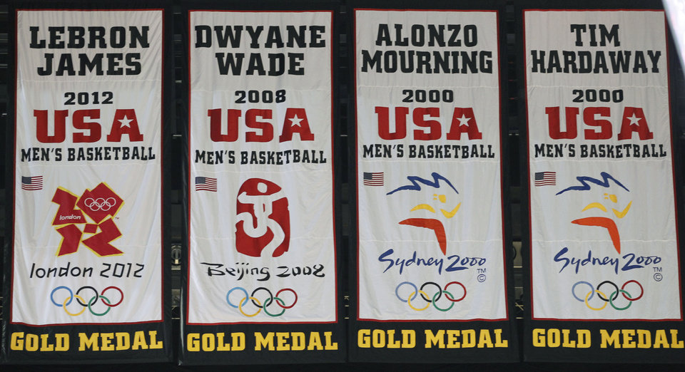 A banner commemorating Miami Heat forward LeBron James\' participation on the gold-medal winning U.S. men\'s basketball team at this summer\'s London Olympics, far left, was unveiled during a ceremony before the start of an NBA basketball game against the Denver Nuggets, Saturday, Nov. 3, 2012 in Miami. His banner sways next to those honoring previous Heat players who were gold-medal winners: Dwyane Wade (2008), Alonzo Mourning (2000) and Tim Hardaway (2000). (AP Photo/Wilfredo Lee)