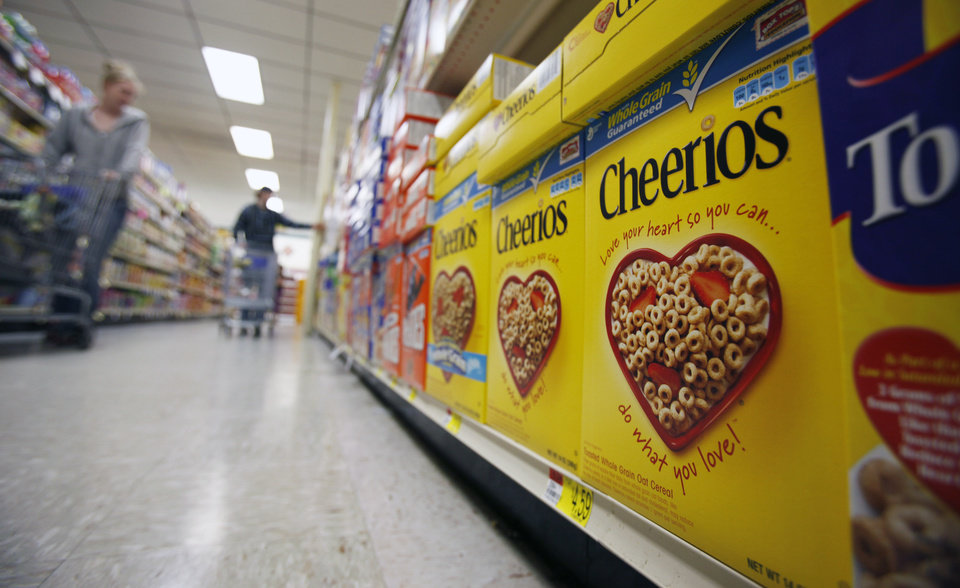 Photo - FILE - This June 16, 2011 file photo shows boxes of Cheerios in a store in Akron, N.Y. Large food companies are trying to head off state-by-state efforts to enact mandatory labeling of genetically modified ingredients by proposing new voluntary labels nationwide. The food industry and farm groups are pushing Congress to pass legislation that would require the Food and Drug Administration to create guidelines for the new labels, which food manufacturers could use. (AP Photo/David Duprey, File)