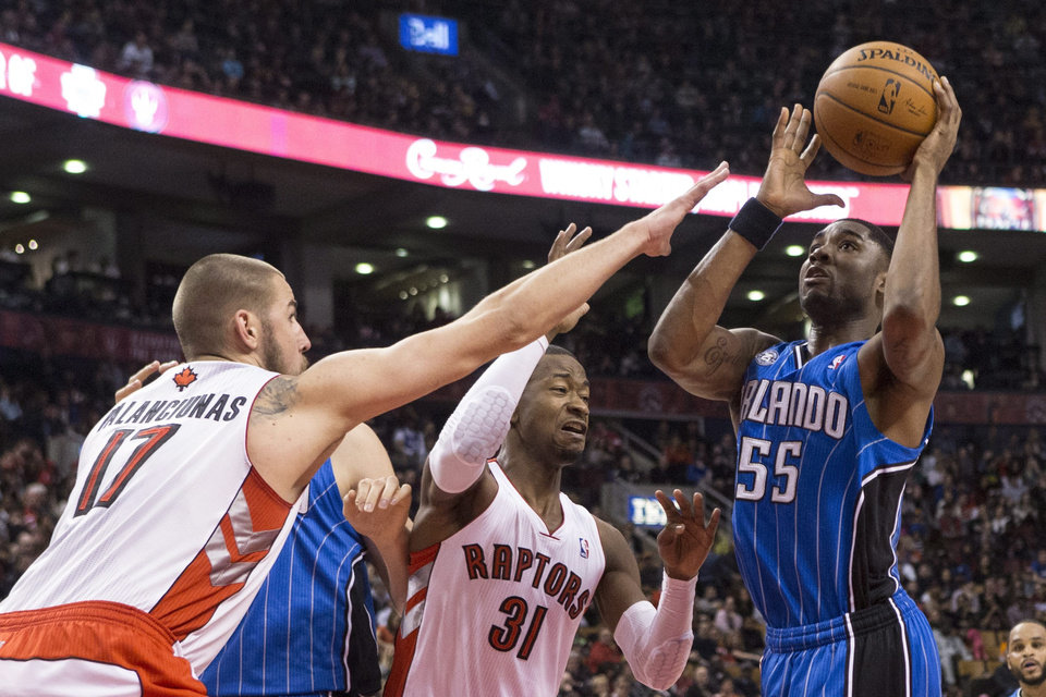Photo - Orlando Magic's E'Twaun Moore, right, shoots as Toronto Raptors' Jonas Valanciunas, left, and Terrence Ross defend during the first half of an NBA basketball game in Toronto, Sunday, Feb. 23 , 2014. (AP Photo/The Canadian Press, Chris Young)