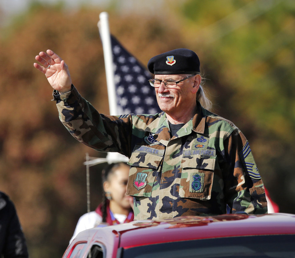 Photo - A man waves from a truck sponsored by the Tinker Inter-Tribal Council during the Midwest City Veteran's Day Parade on Friday, Nov. 10, 2017. Photo by Jim Beckel, The Oklahoman