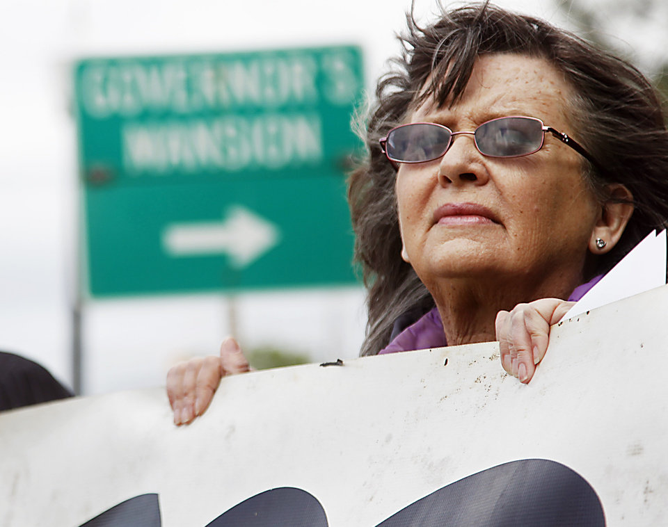 Photo - Fannie Bates of Oklahoma City holds a sign urging Gov. Mary Fallin to issue a stay in the execution of two inmates, during a protest Tuesday, April 29, 2014, near the Governor's Mansion in Oklahoma City. A botched execution that used a new drug combination left an Oklahoma inmate writhing and clenching his teeth on the gurney later Tuesday, leading prison officials to halt the proceedings before the inmate's eventual death from a heart attack. (AP Photo/The Oklahoman, KT King)