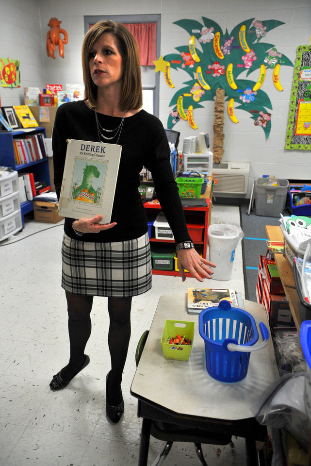 Midland City Elementary School kindergarten teacher Suzanne Dasinger talks about her student who had beren held hostage  as she holds one of his favorite books next to his desk in her classroom on Tuesday afternoon Feb. 5, 2013 in Midland City, Ala.   The boy was held for a week in a closet-size bunker underground, a captive of a volatile killer.  (AP Photo/The Dothan Eagle, Jay Hare)  MAGS OUT TV OUT