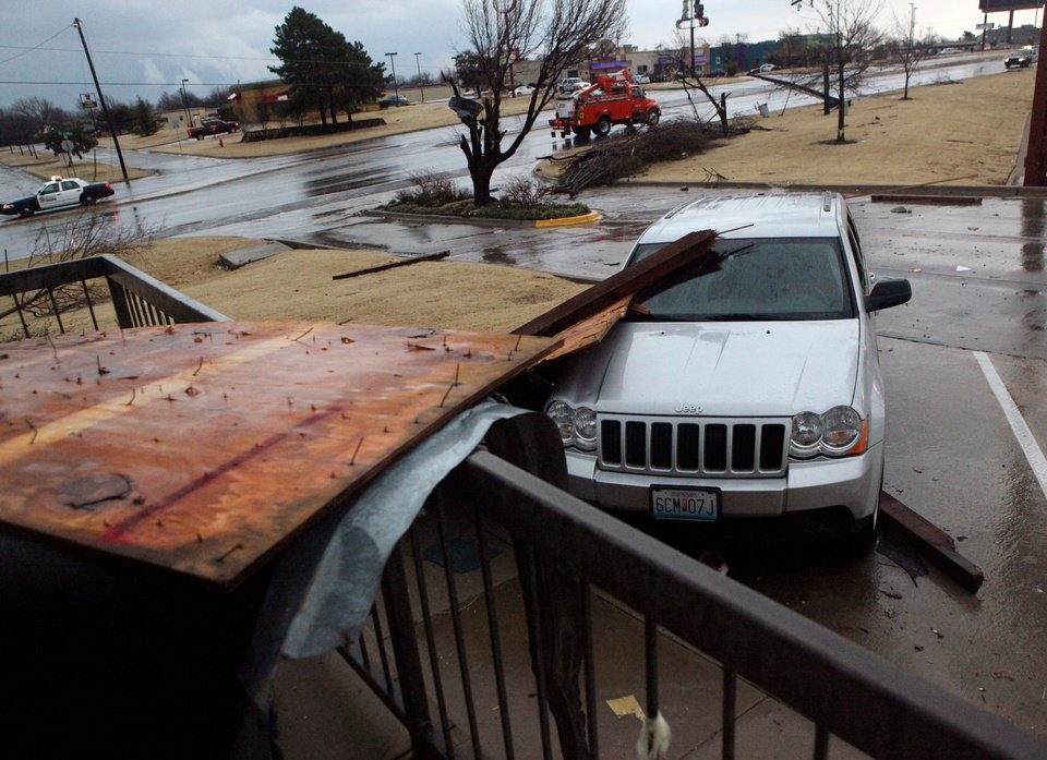 Photo - Pieces of a shopping center lie on a car near Northwest Expressway and Rockwell following storms  in Oklahoma City on Tuesday, Feb. 10, 2009. By John Clanton, The Oklahoman