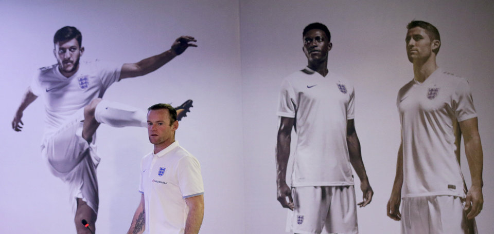 Photo - England national soccer team player Wayne Rooney walks past images of his England teammates, from left, Adam Lallana, Danny Welbeck and Gary Cahill upon his arrival to speak in a press conference after a training session for the 2014 soccer World Cup at the Urca military base in Rio de Janeiro, Brazil, Wednesday, June 11, 2014.  The England soccer team are staying in Rio de Janeiro as their base city for the 2014 soccer World Cup.  (AP Photo/Matt Dunham)