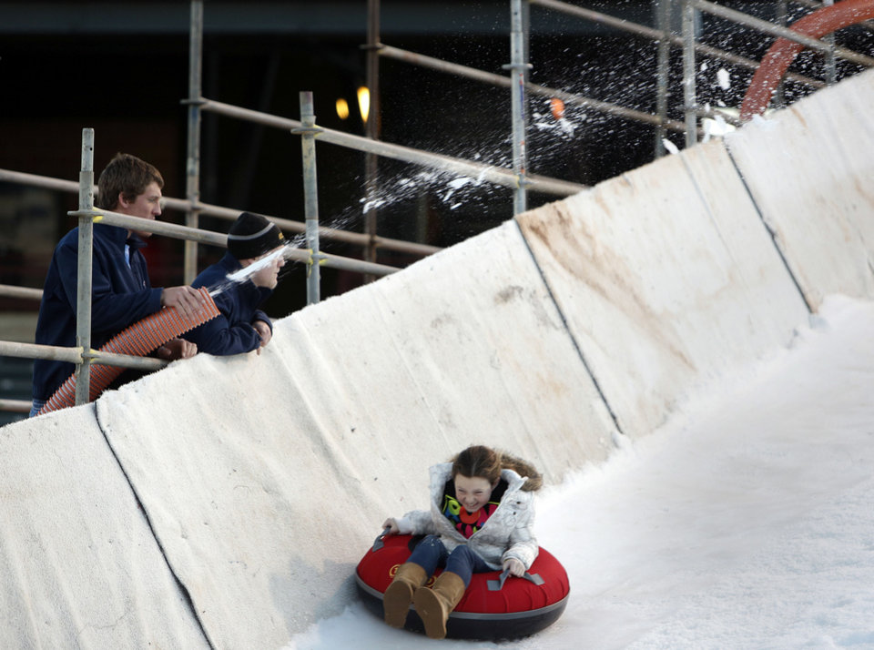 Employees spray snow on a slope as Macy McColl, 9, rides down at Chickasaw Bricktown Ballpark. Photo by Garett Fisbeck, The Oklahoman <strong>GARETT FISBECK - GARETT FISBECK</strong>