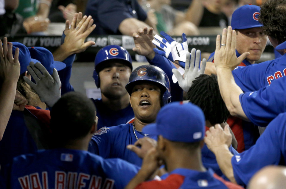 Photo - Chicago Cubs' Starlin Castro, center, is congratulated in the dugout after hitting a two-run home run off Chicago White Sox starting pitcher Scott Carroll during the fourth inning of an interleague baseball game Thursday, May 8, 2014, in Chicago. (AP Photo/Charles Rex Arbogast)