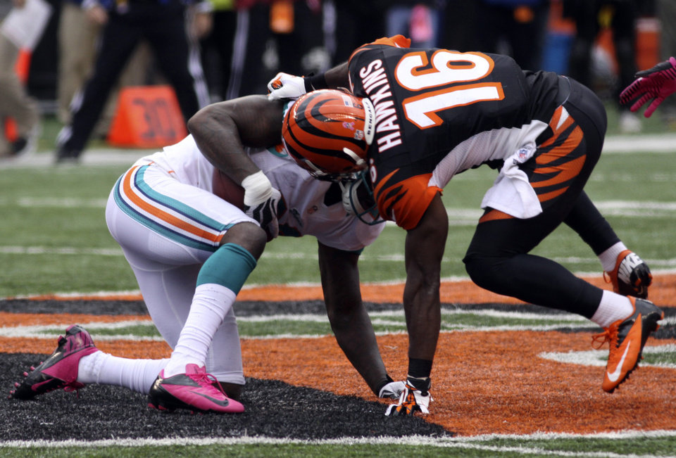 Photo -   Miami Dolphins free safety Reshad Jones, left, intercepts a pass intended for Cincinnati Bengals wide receiver Andrew Hawkins (16) in the end zone in the closing minute of an NFL football game on Sunday, Oct. 7, 2012, in Cincinnati. Miami won 17-13. (AP Photo/Tom Uhlman)