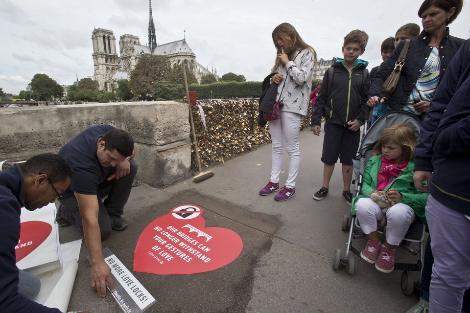 Photo - Passers-by look on municipality workers, as they fix a giant sticker on the sidewalk of the Pont de l'Archeveche in Paris, Wednesday, Aug. 13, 2014. Paris is hoping to persuade visiting couples to end the recent and unwelcome tradition of fixing padlocks to the Pont de l'Archeveche. With giant stickers in three languages in French, English and Spanish. Paris began its 'Lovewithoutlocks' campaign, saying the city's famed bridge could not withstand the thousands of padlocks that cling to every available surface. (AP Photo/Michel Euler)